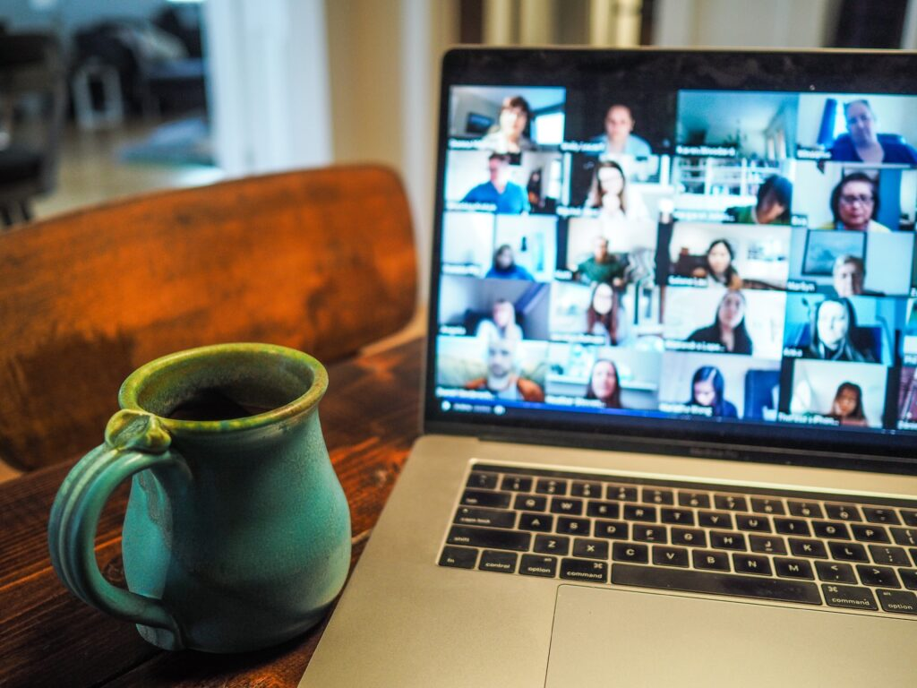 laptop screen showing a virtual meeting in progress. A mug sits on the table next to the laptop.