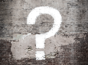 White painted question mark on distressed wall