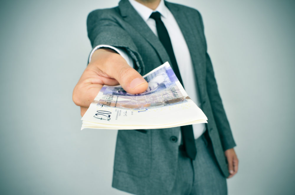 A man in a suit holding out some money