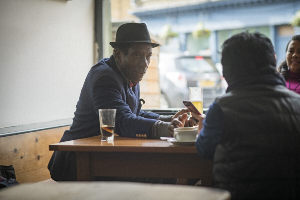 Three people sitting at a cafe table. One is showing the other two something on a smartphone screen